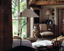 Antique collectors' items in small, cosy living room with exposed ceiling beams and terrace door leading to garden