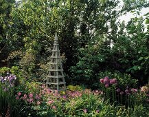 Wooden trellis obelisk in front of trees in cottage garden