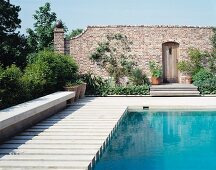 Pool with wooden decking sheltered by brick wall with creepers and doorway with wooden door