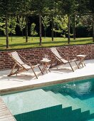 Deckchairs next to pool with masonry steps and lawn with trees