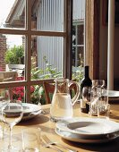 Simple crockery, glasses and jug of water on wooden table, view through window