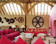 Converted barn with pink sofas and antique table against half-height partition with old cogwheels