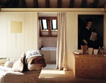 Portrait print above modern, wooden chest of drawers and view into ensuite bathroom