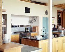 Modern country house kitchen with wooden doors and black stone work surface on sink unit