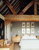 Modern bedroom with light wooden furniture beneath old, heavy roof timbers