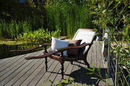 Lounger with cushions next to garden pond