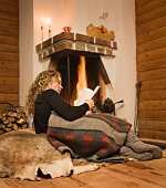 Woman lying in front of fire on fur reading book