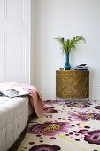 Carpet with floral pattern and semi-circular console cabinet in bronze-coloured metal