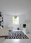Black and white patterned rug in front of white leather armchairs in cool living room