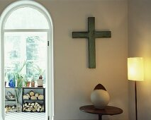 Cross on wall in corner of room and arched doorway leading to loggia