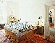 Double bed with ethnic bedspread next to open door in bedroom