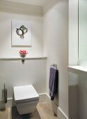 White wall-mounted toilet in modern bathroom