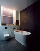 Free-standing bathtub on grey tiled floor in front of dark grey wall