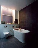 Free-standing bathtub on grey tiled floor in front of dark grey wall