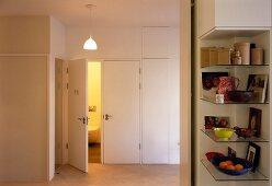 Hallway with shelves built into niche and open toilet door