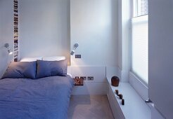 Bed with grey bed linen in white bedroom
