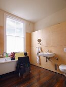 Drying rack in bathtub and sink on modern, wooden installation against wall