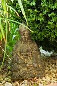 Oriental art- small, stone Buddha figurine on gravel