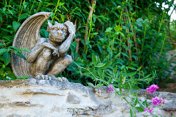 Bronze mythological figurine on garden wall