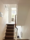 Dark stair runner on white-painted wooden stairs in traditional stairwell