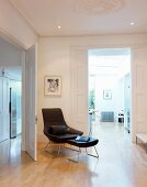 Designer leather armchair and matching footstool in traditional anteroom