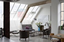 Open-plan living space with furniture in a mix of styles under glazed sloping ceiling