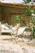 Bank und Liegestuhl auf einer überdachten Terrasse mit Natursteinmauer