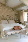 Doppelbett mit Ablagebank in einem Schlafzimmer mit Natursteinwänden unter dem Dach