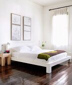 Corner of modern bedroom with modern double bed on glossy floorboards