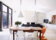 Dining area with rustic wooden table in modern room with fireplace