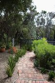 Path of terracotta tiles in Mediterranean garden