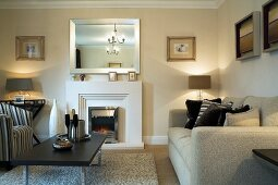 Modern coffee table and sofa in room with fireplace