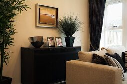 Light sofa in front of black sideboard