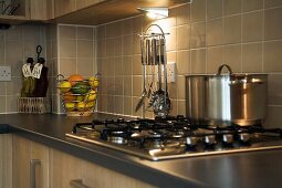 Kitchen counter with gas hob in front of light brown tiled wall