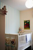 Cot made of white-painted slats against wall with striped wallpaper