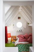 Cosy child's sleeping cabin with porthole under pointed, wooden attic roof