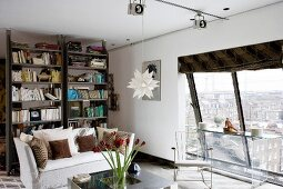 Youthful, modern living room with view of cityscape through slanting panoramic window