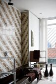 Dark brown bathtub and stainless steel towel rail against 70s, retro-style brown and white tiled wall