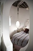 Keyhole-shaped doorway into lovingly decorated sleeping cabin with fabric canopy