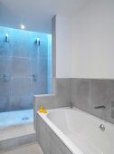 Grey-tiled, minimalist bathroom with open shower area lit from above