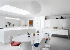 Modern designer kitchen and dining area with fifties retro furniture in open-plan white room