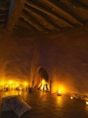 Burning fire in fireplace aperture and candlelight in clay house with simple roof structure