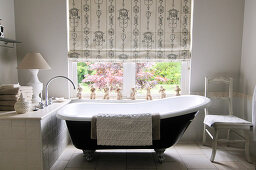 Free-standing, vintage bathtub in front of window with blind in modern setting