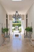 Metal chairs on marble floor in foyer of country house with open terrace doors