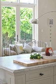 Kitchen island with marble top and metal-framed bench in front of terrace door
