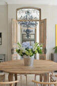 Bouquet on round wooden table in front of open, interior double doors