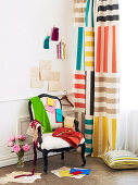 Various swatches of fabric on antique chair with white upholstery next to curtain with multi-coloured stripes