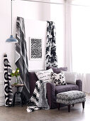 Black and white patterned lengths of fabric next to upholstered armchair with scatter cushions and footstool
