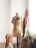 Tailor's studio - fabrics on wicker trunk and stool next to tailor's dummy and bolts of cloth in corner