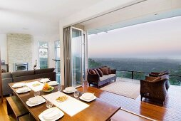 Panoramic view of landscape across balcony from open-plan dining room